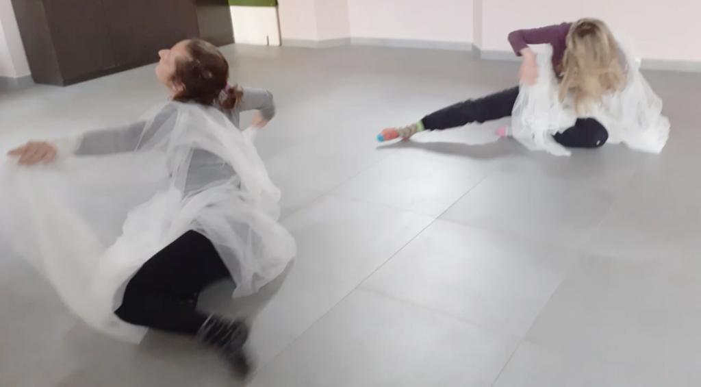 due donne che danzano a terra in un ambiente al chiuso coperte da veli di tulle