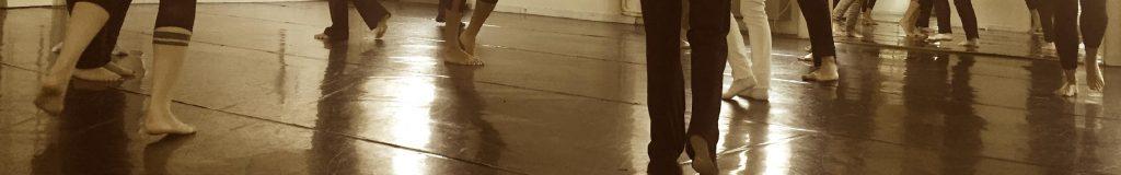 gambe di persone durante una lezione di danza, in tenuta sportiva e a piedi nudi in una stanza con pavimento di legno e specchi alle pareti